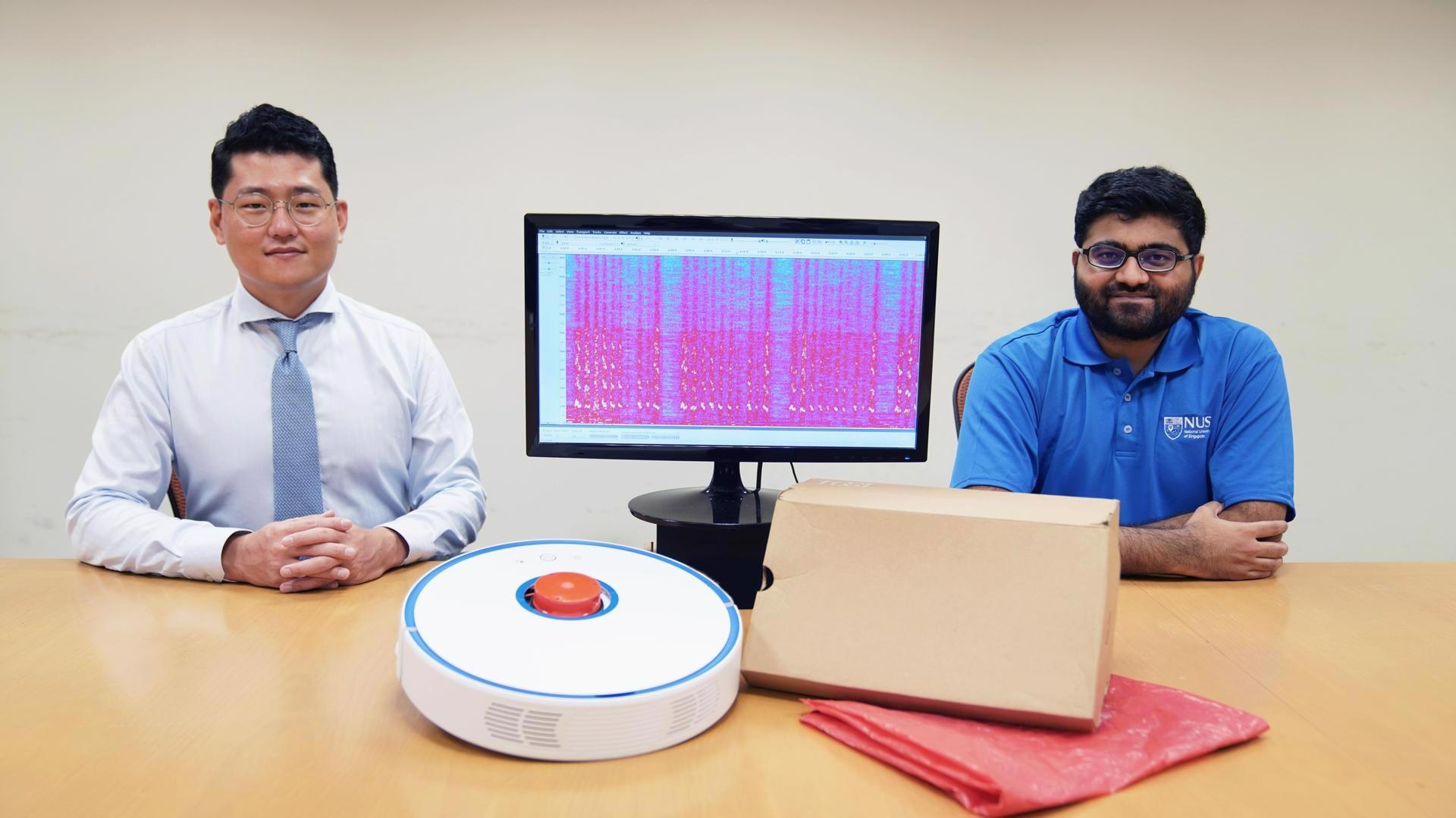 Assistant Professor Jun Han (left) and doctoral student Mr Sriram Sami (right) from NUS Computing with a robot vacuum cleaner, a monitor showing recovered sound waves, and common household items made from materials that can reflect sound. Image Credit: National University of Singapore.